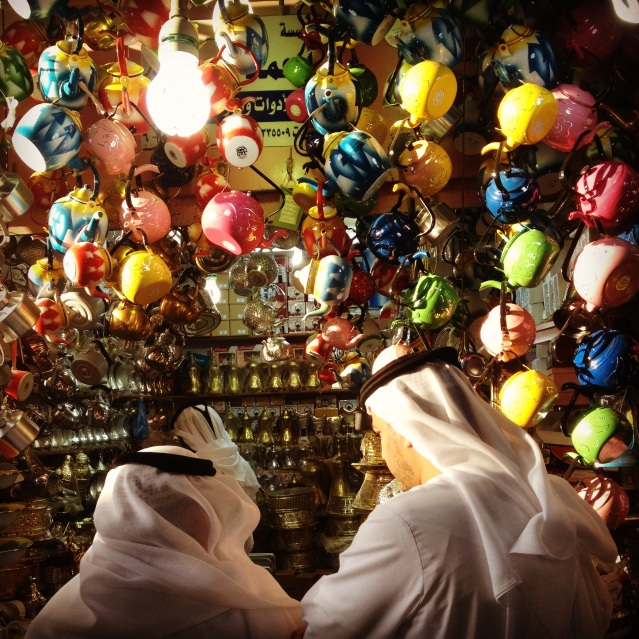 two men ponder buying a tea pot at the old souq
