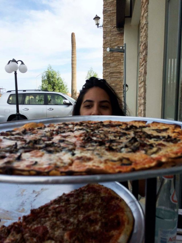 my view at lunch: yasmine, two giant pizzas, and a frondless palm