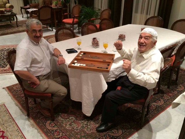 musa and sido play backgammon, sido does a sitting dance