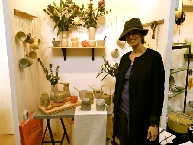 sarah in her new hat by elizabeth renton's ceramic display. it was the pomegranates that attracted our attention to this thoughtfully put-together booth