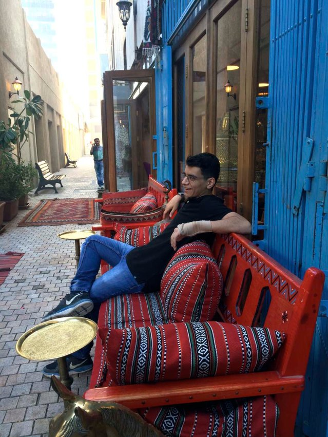 while yousef sits on a more practical bench with traditional sadu cushions