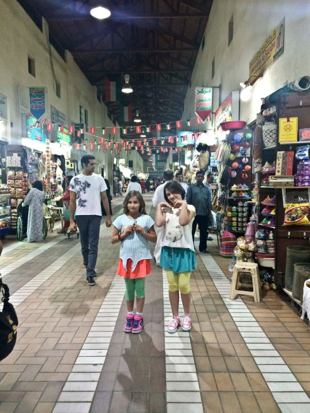 colorful girls, teapots and bunting in one of mubarakiya's many corridors